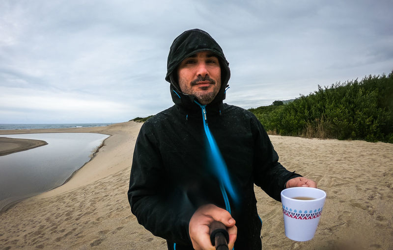 Portrait Of Man Having Coffee While Standing At Beach Against Sky