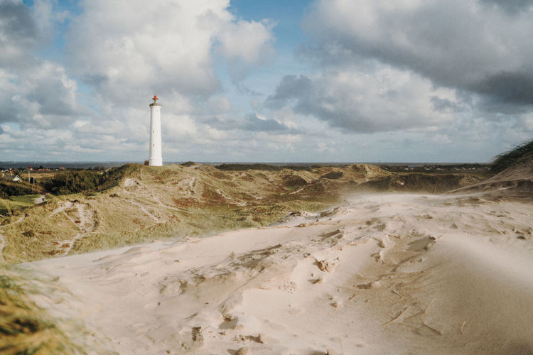 Lighthouse in Denmark between dunes Cloud - Sky Sky Land Tower Lighthouse Direction Day Nature Guidance Beach Scenics - Nature Water Beauty In Nature Architecture Building Exterior Sea Built Structure Tranquility Sand No People Outdoors Denmark Dunes North Sea