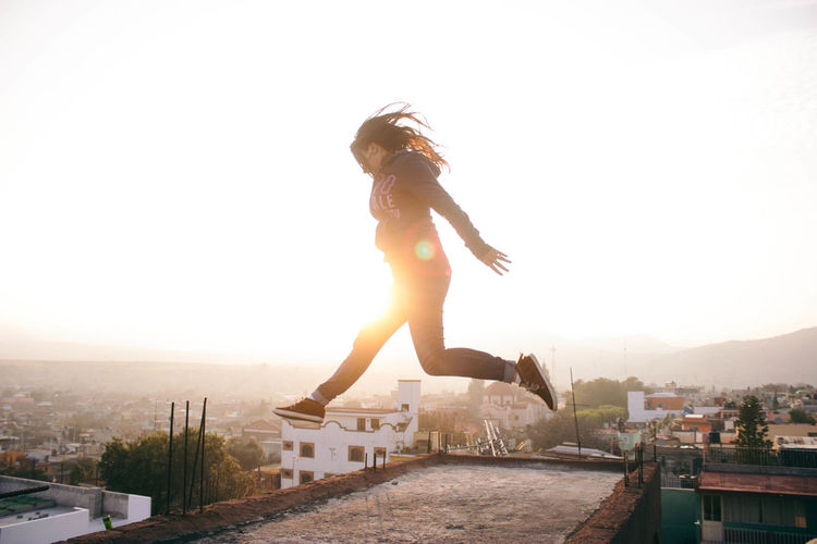 Girl jumping when the sun goes down. Adult Adults Only Beautiful Woman City Cityscape Clear Sky Day Freedom Jumping Lens Flare Motion One Person One Woman Only One Young Woman Only Only Women Outdoors People Sky Summer Sun Sunbeam Sunlight Sunset Young Adult Young Women Live For The Story