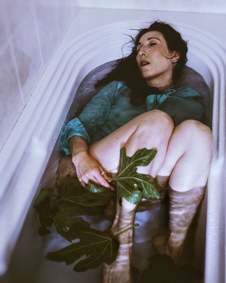 High angle view of woman sleeping in bathtub