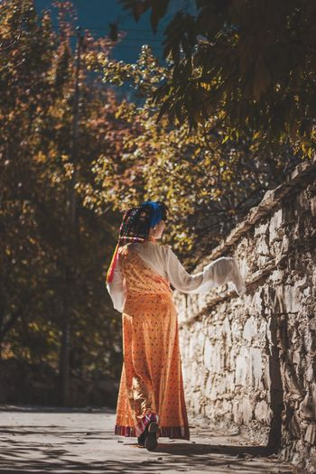 Rear view of woman in traditional clothing walking on footpath