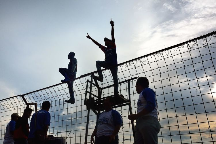 Low angle view of cheerful spectators by fence against sky