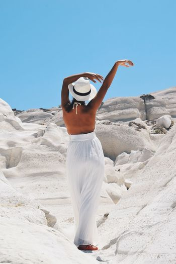 Rear View Of Woman Standing On Amidst Rock Against Clear Sky