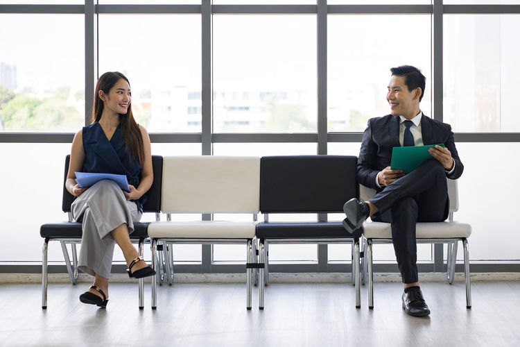 Full length of cheerful business people sitting on chair