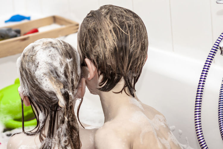 Siblings taking bath in bathroom at home