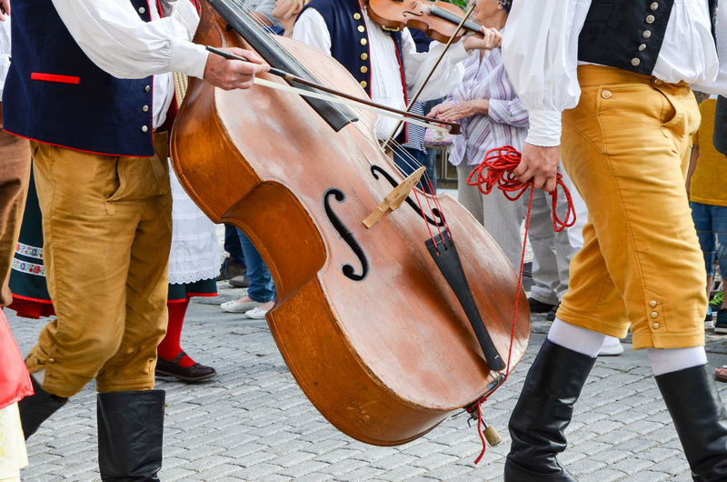 Midsection of musicians playing cello in city
