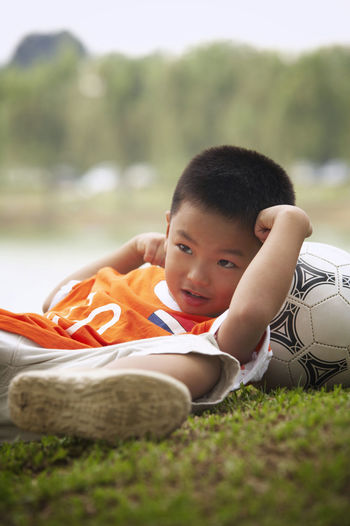 Full Length Of Boy With Soccer Ball Lying On Field At Park