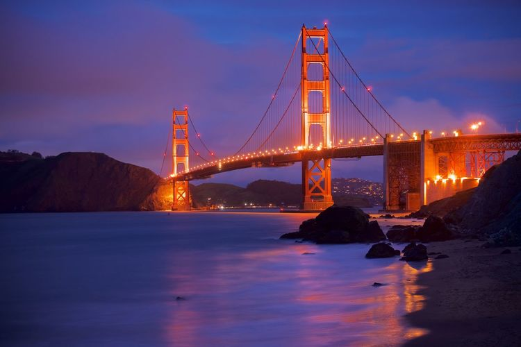 Illuminated golden gate bridge over bay against cloudy sky during dusk