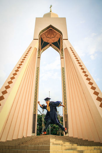 Low angle view of man in graduation gown running against entrance and sky