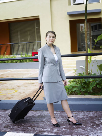 Full length portrait of confident businesswoman walking with wheeled luggage against building