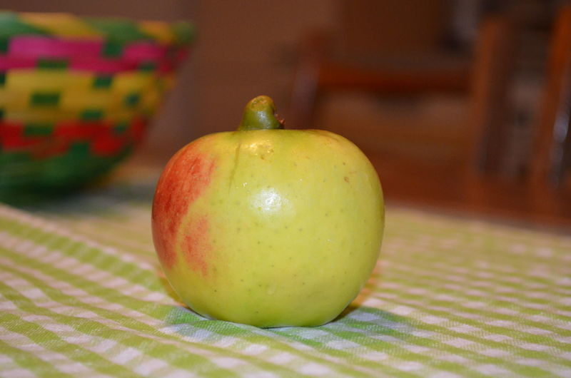 An apple on a table Apple Apple - Fruit Apple On Table Focus On Foreground Food Freshness Green Green Color Organic Selective Focus Table First Eyeem Photo