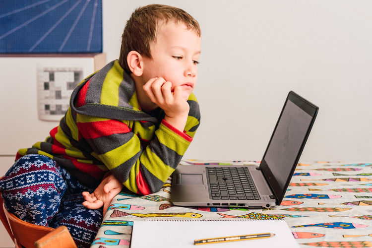 Full length of boy using mobile phone while sitting on table