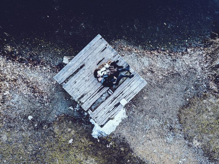 Directly above view of young couple lying on floorboard at riverbank
