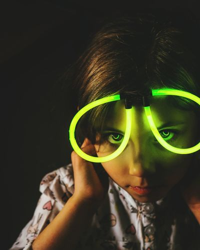 Close-up portrait of girl wearing illuminated glasses