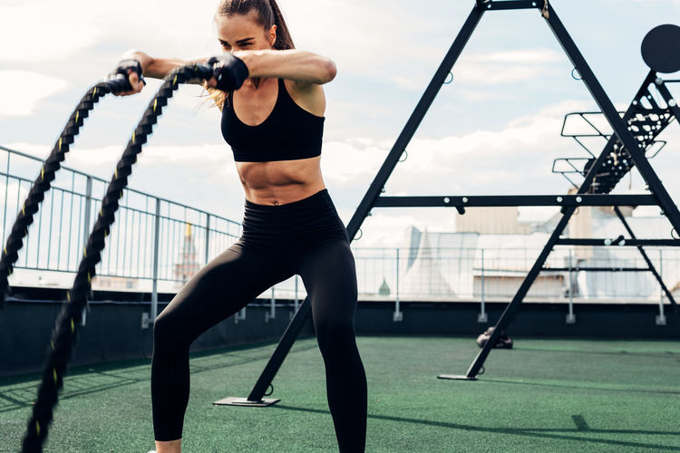 Woman exercising on building terrace against sky