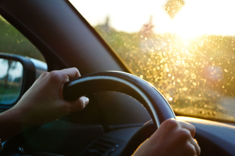 Cropped Hands On Steering Wheel At Morning