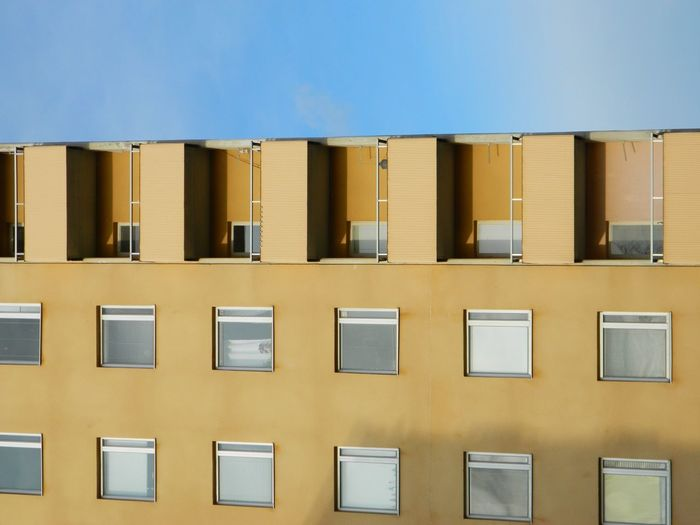 Low angle view of yellow building against clear sky