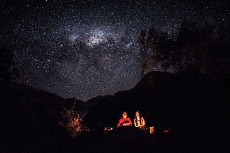 Silhouette people on mountain against sky at night