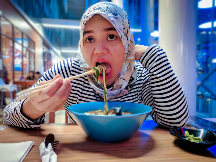Portrait of woman eating noodle in bowl on table