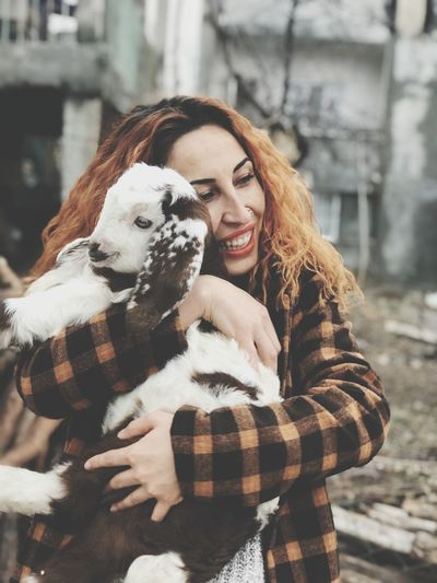 Smiling young woman embracing kid goat in winter