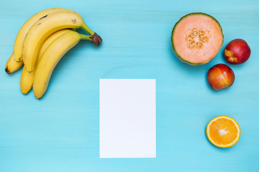 Cyan tabletop with fruit and a white paper Orange Banana Bananas Blank Blank Paper Colored Background Cyan Cyan Table Directly Above Flat Lay Flatlay Food Food And Drink Freshness Fruit Healthy Eating Healthy Lifestyle Indoors  No People Tabletop Scene White Paper Yellow
