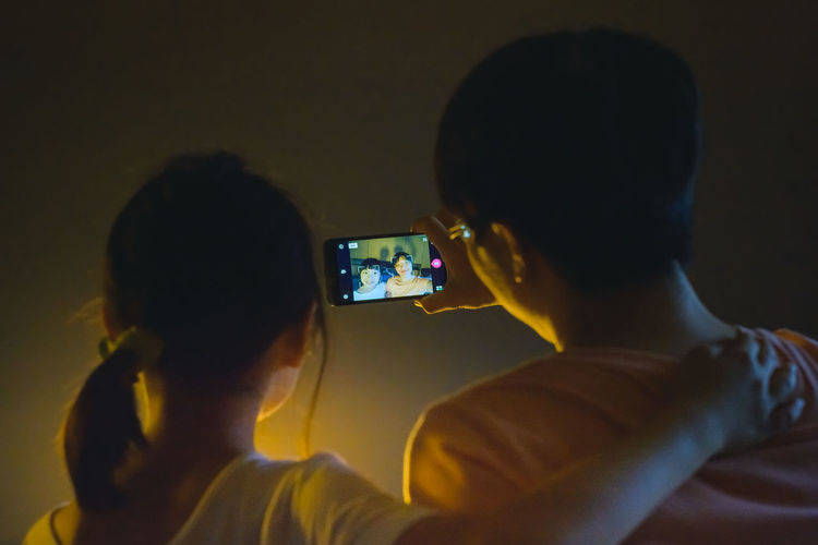 Mother and daughter take a selfie by using smartphone Asian  Children Woman Camera - Photographic Equipment Darkness And Light Device Screen Dougter Family Time Girl Headshot Holding Illuminated Leisure Activity Lifestyles Mobile Phone Mothernature Night Photographing Real People Rear View Selfie Smart Phone Togetherness