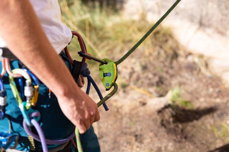 Midsection of man with climbing equipment standing outdoors