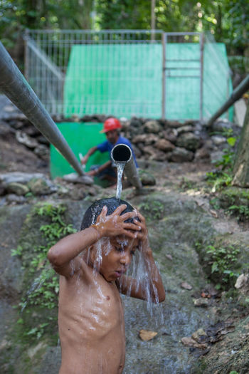 Shirtless boy standing under falling water from pipe