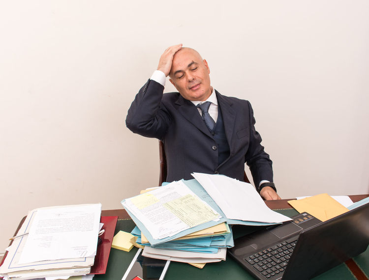 Bald Bald Head Baldhead Baldness Business Businessman Day Desk Eyeglasses  Front View Indoors  Loss One Person People Sitting Stack Studio Shot Tensed Well-dressed White Background Young Adult