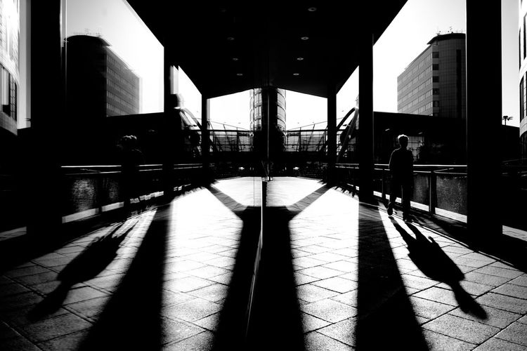 Silhouette man walking on tiled floor in city