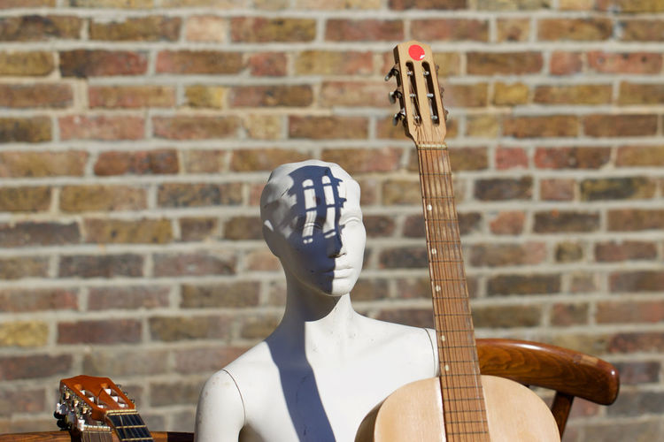 Mannequin with guitar on sunny day against brick wall