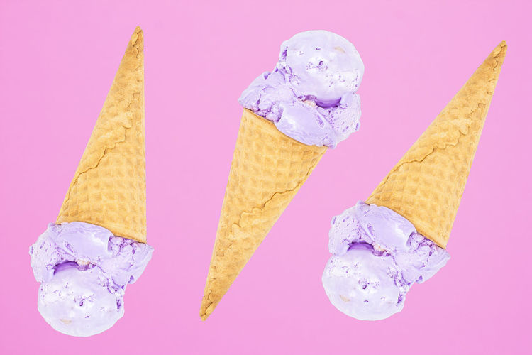 High angle view of ice cream cone against colored background