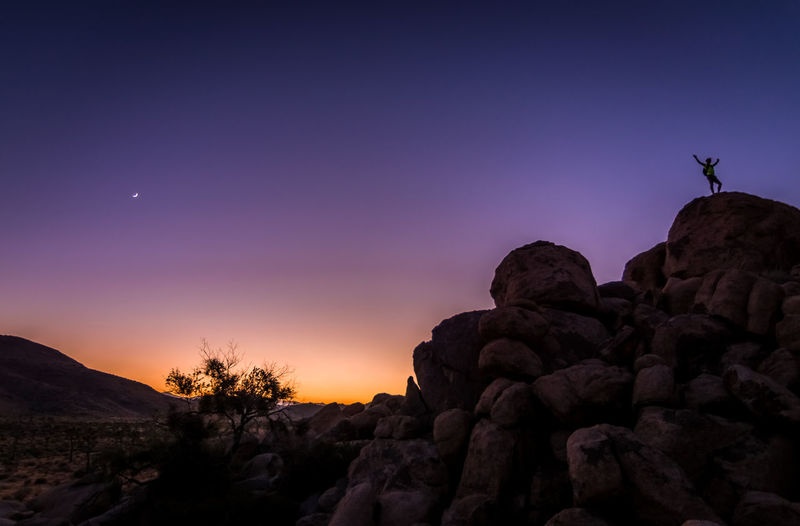 Silhouette rocks on mountain against clear sky during sunset