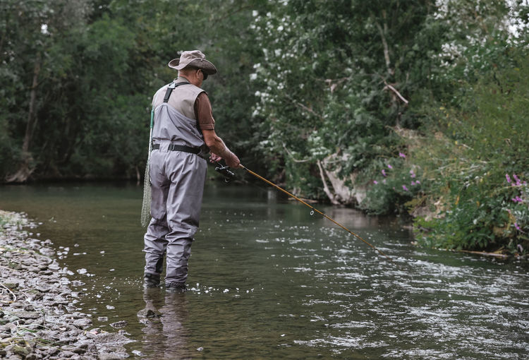 // der Fischer Fritz fischt frische Fische // Country Green Peace Activity Casual Clothing Day Fish Fisherman Fishing Full Length Hat Lake Men Nature One Person Outdoors Plant Real People River Sea Standing Summer Tree Water Waterfront