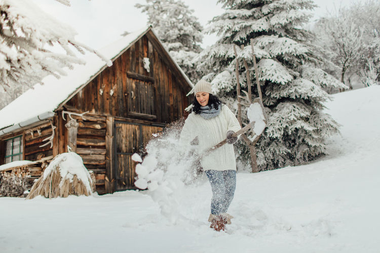 Smiling young woman playing with snow