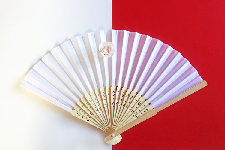 High angle view of hand fan on colored background