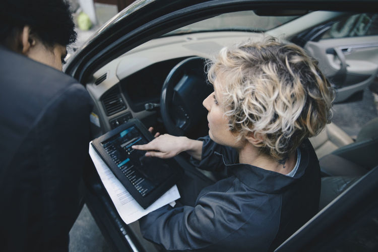 Rear view of woman using mobile phone in car