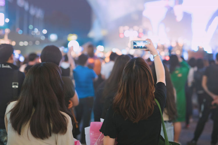 Nightlife and activity of people in new normal with asian woman take photo in outdoor concert