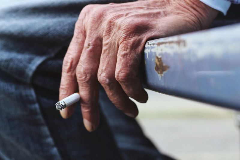 Cropped image of man holding cigarette