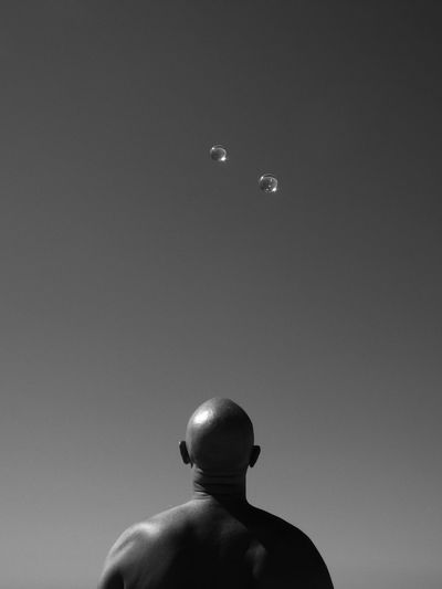 Rear View Of Bald Man Looking At Bubbles Against Sky