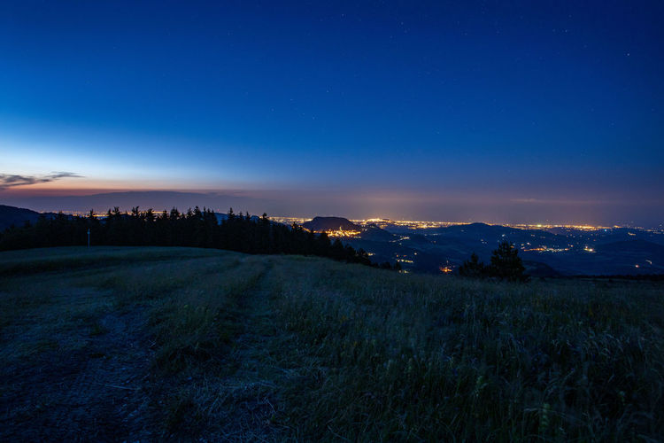 Scenic view of landscape against blue sky at night