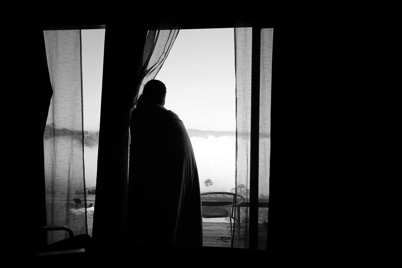 REAR VIEW OF SILHOUETTE MAN LOOKING THROUGH WINDOW AT SUNSET