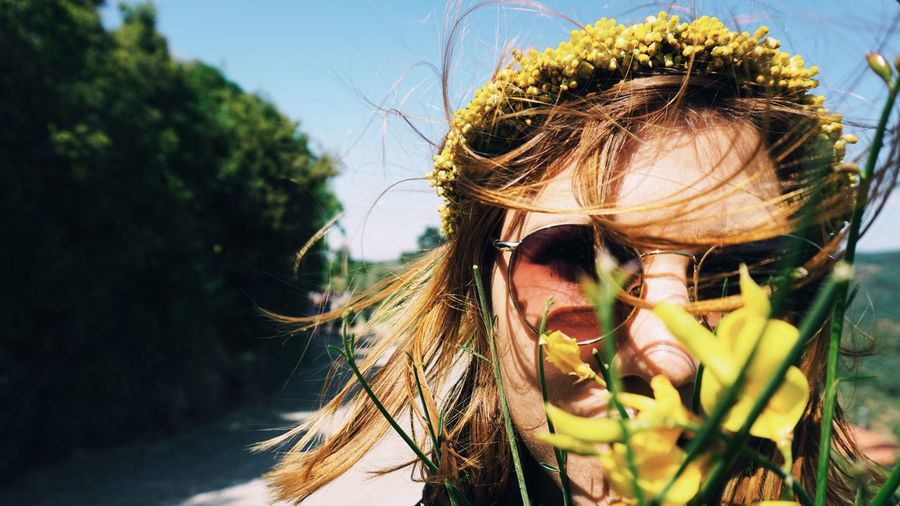 Close-up portrait of woman in sunglasses by flowers