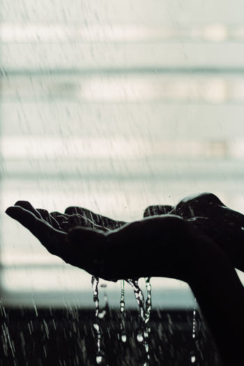 Close-up of water drop falling from hand
