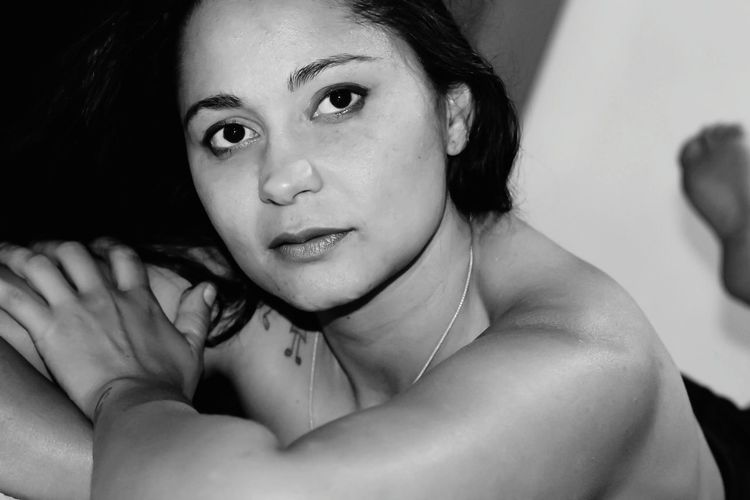Portrait of topless young woman lying at home