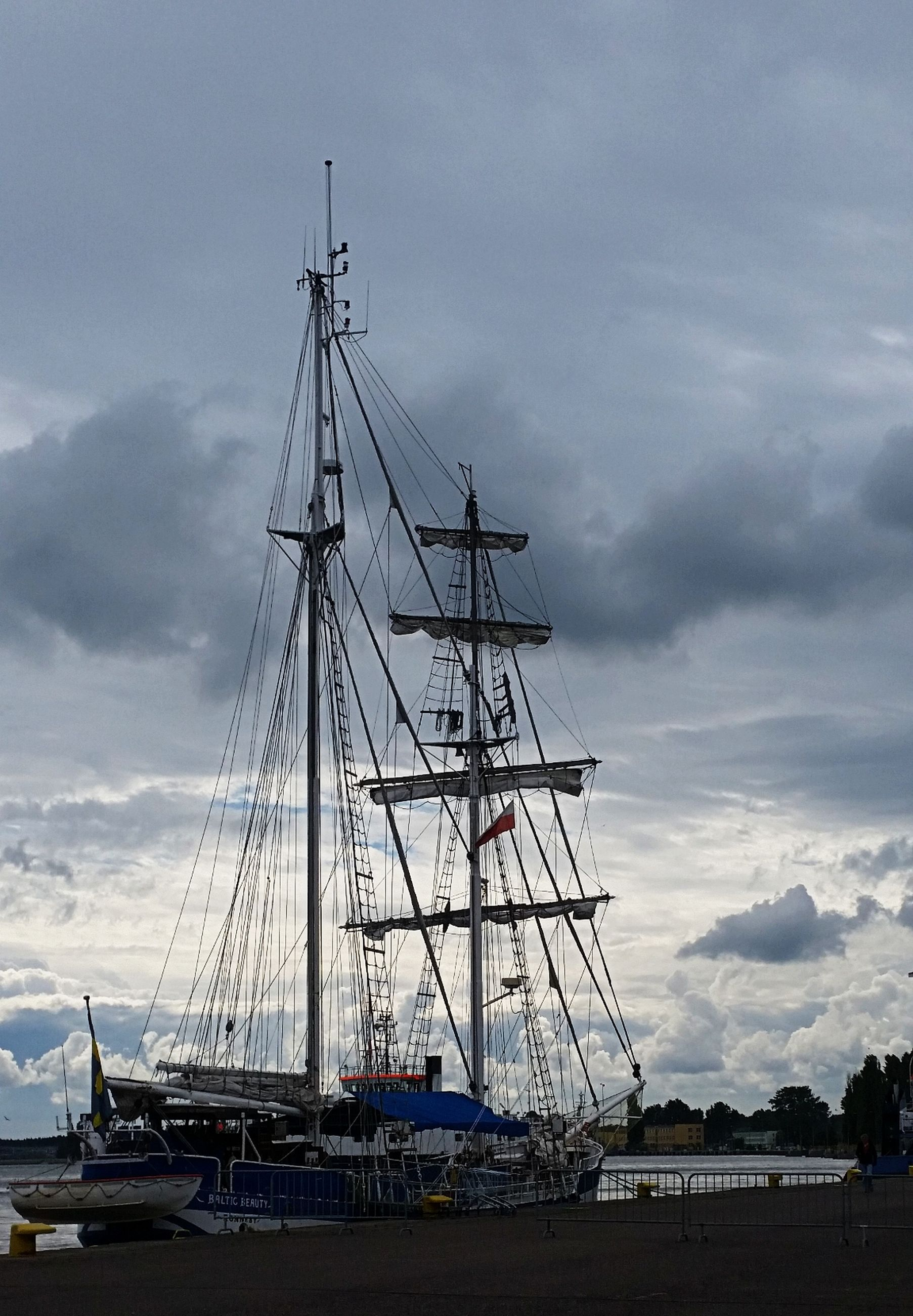 nautical vessel, transportation, mode of transport, mast, sky, moored, cloud - sky, cloud, nature, day, ship, cloudy, outdoors, tall - high, scenics, harbor, no people, non-urban scene, tranquility, tranquil scene, beauty in nature