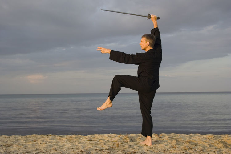 Man practicing tai chi on sand at beach
