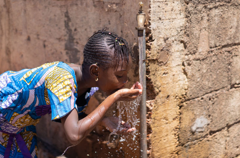 Girl drinking water from faucet against wall