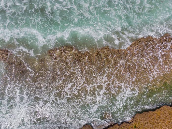 High angle view of waves splashing on rocks