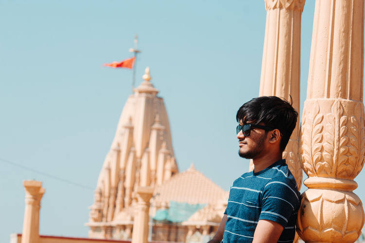 Young man wearing sunglasses looking away with temple in background